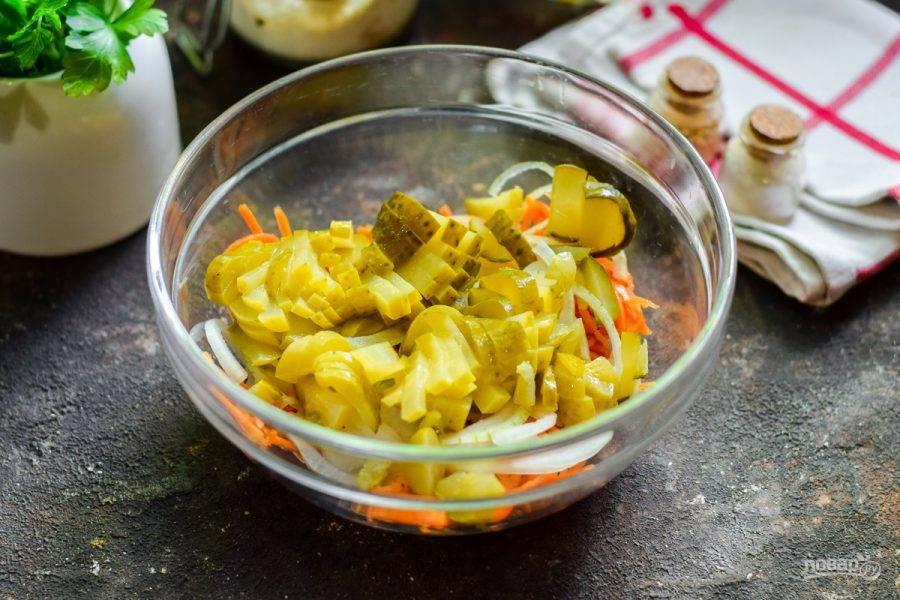Следом нарежьте маринованные огурцы полосками, добавьте в салат.
