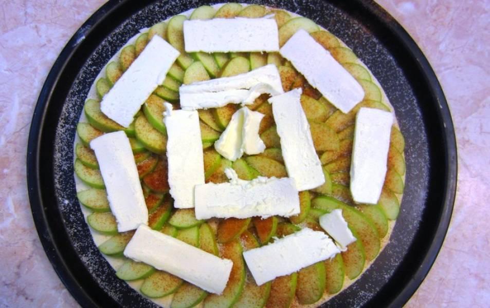 Поверх теста уложите яблоки, посыпьте сахаром, корицей и цедрой. Уложите кусочки сливочного масла. Запеките в духовке 25 минут при 200 градусах. Готовый пирог полейте горячим джемом.  Перед подачей охладите до комнатной температуры.