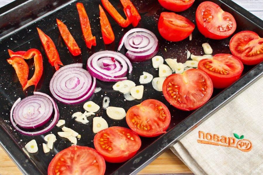 Перец нарежьте на полоски, лук - кольцами, чеснок измельчите, помидоры - на половинки. Разложите овощи на противне, посолите и поперчите, полейте оливковым маслом.  Поставьте запекаться их в разогретую до 180 градусов духовку на 30 минут до мягкости томатов. Тонкие ломтики чеснока приготовятся раньше, выньте их из духовки сразу после зарумянивания.