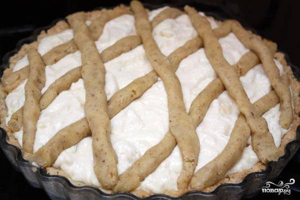 На испеченное тесто равномерно распределяем нашу творожную начинку. Сверху украшаем пирог сеточкой из оставшегося теста - как на фото.