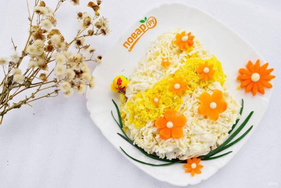 """4-й слой — тертый плавленый сырок. Сверху сделайте полоску из тертого желтка и украсьте цветами из моркови. Снизу """"яйца"""" разместите перья зеленого лука."""