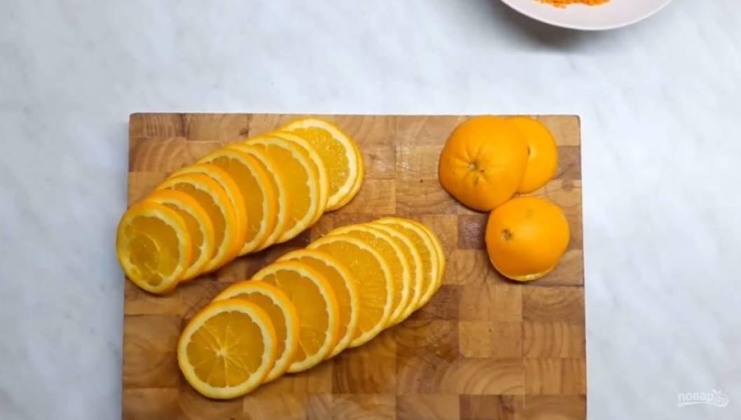 2. Два апельсины нарежьте кружочками 3-4 мм толщиной. Снимите цедру с лимона. Еще один апельсин разрежьте пополам, выньте из него мякоть и выдавите сок.