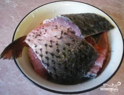 Прежде всего, тушку рыбы необходимо почистить, выпотрошить, хорошенько промыть и обсушить. После этого удалить голову, хвост и плавники (при желании можно и хребет утилизировать), нарезать карпа довольно крупными кусками. Вообще, можно и не резать, если карпы небольшие.