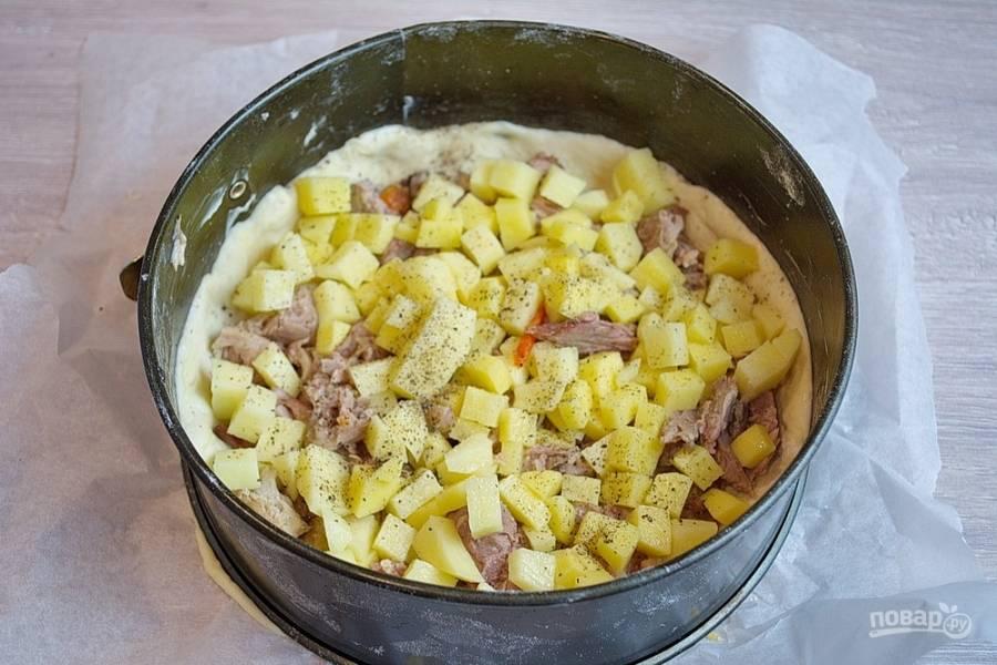 Разделите тесто на два куска. Из этого теста у меня вышло 2 курника. Одну часть теста раскатайте в пласт толщиной 1,5 см. Уложите тесто в форму. Обрежьте лишнее. На тесто выложите нарезанную отварную курицу и картофель. Посолите, поперчите по вкусу.