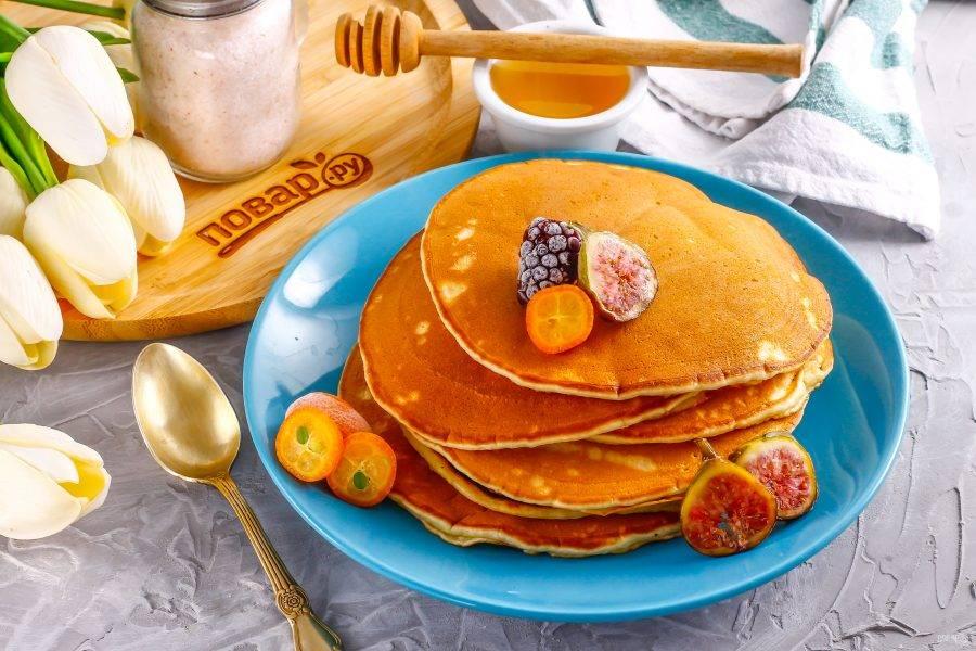 Выложите горячие панкейки на тарелку и подайте с ягодами, медом к столу.