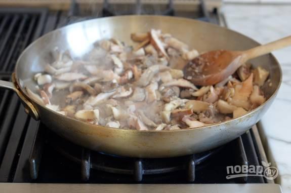 3. После этого добавьте на сковороду нарезанные грибы. Обжарьте ингредиенты ещё пару минут, помешивая.