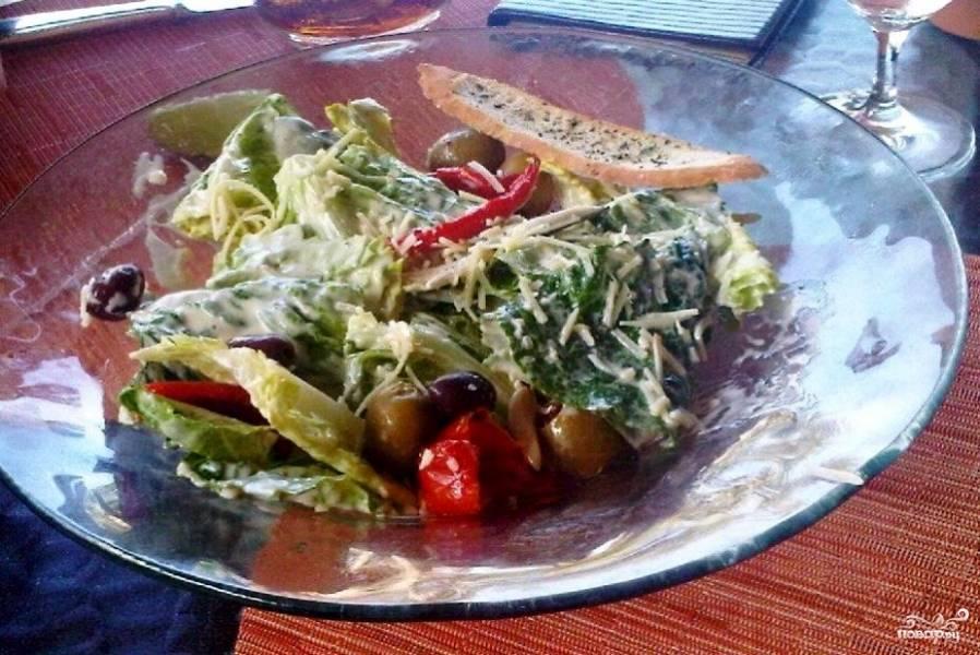 """Салат полить соусом и осторожно перемешать. Выложить на салатные листья крутоны и оливки. Полить остатками соуса. Посыпать тертым пармезаном.  Салат """"Цезарь"""" с оливками готов!"""