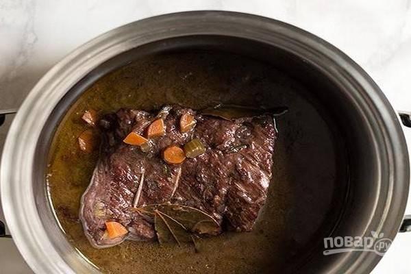 Продолжайте готовить мясо на среднем огне, пока вино не выпарится и не исчезнет запах алкоголя. Теперь уменьшите огонь до минимума, накройте мясо крышкой и тушите 2-2,5 часа, переворачивая его каждые полчаса. В середине приготовления добавьте соль. Готовое мясо должно получиться очень мягким. Выключите огонь и дайте мясу остыть 30 минут.