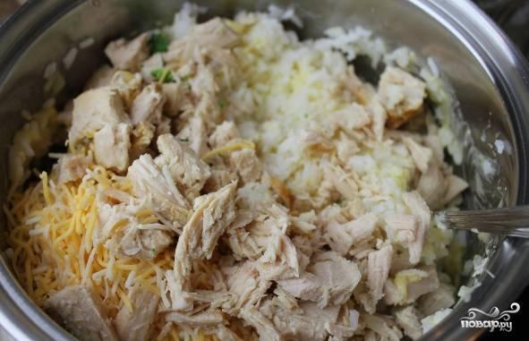 Сыр натрите на терке, смешайте вместе с рисом курицу, сливки и половину от полученной сырной стружки. Добавьте в смесь соль и перец.