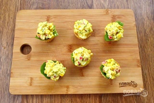 Перед подачей на дно тарталетки положите по листику шпината или салата, разложите салат.