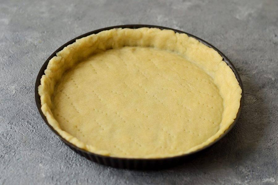 Раскатайте тесто и выложите в форму для запекания. Сформируйте бортики, дно наколите вилкой. Выпекайте корж в духовке 10 минут при температуре 200 градусов.