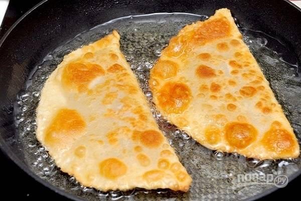 Налейте в сковородку масло и подождите, пока оно хорошенько разогреется. Жарьте чебуреки до коричневато-золотистого цвета с обеих сторон.