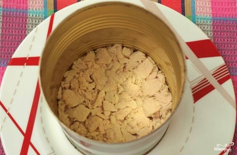 Копчёное куриное мясо нужно отделить от костей и нарезать небольшими кусочками. Подготовьте тарелку, в которой будет подаваться салат. Также понадобится салатное кольцо. Его можно вырезать из пластиковой бутылки или жестяной банки. Кольцо установите на тарелку и выложите первый слой: куриное мясо. По желанию на слой положите несколько грамм майонеза.