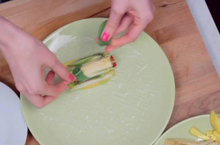 3. Аккуратно заверните рисовую бумагу в форме ролла и выложите на тарелку так, чтобы роллы не соприкасались друг с другом.