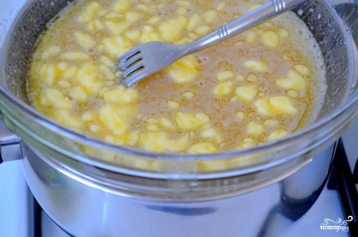 Для приготовления теста взбейте яйца веничиком. К ним добавьте мёд, сахар и сливочное масло. Поставьте всё на водяную баню и, постоянно помешивая, дайте маслу растаять.