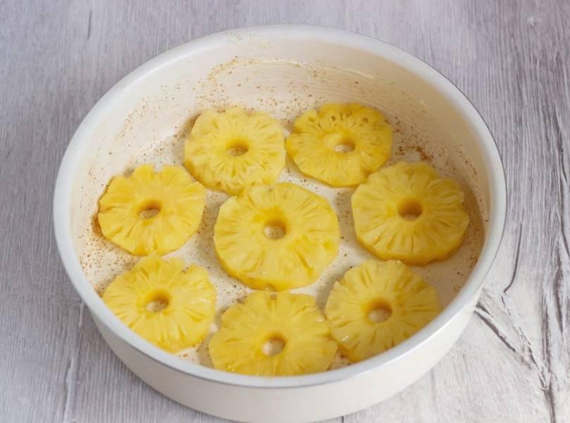 Форму (26 см. диаметром, можно 24 см.) смажьте сливочным маслом, посыпьте панировочными сухарями и выложите на дно кольца консервированного ананаса.