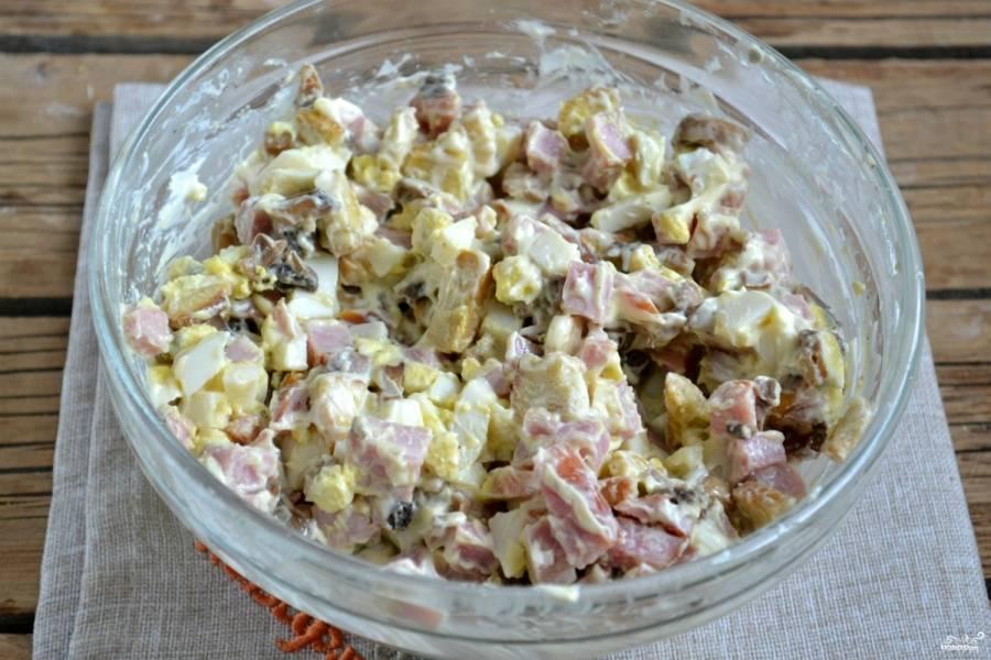 Хорошо перемешайте получившуюся массу. Затем выложите салат на плоскую тарелку, посыпьте тертым сыром.