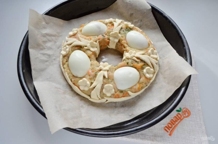Оформите пирог полосочками теста, оно отлично прилипает и хорошо держится. Из оставшегося теста формой для печенья выдавите цветочки. Украсьте пирог цветочками. Желтком смажьте тесто, отправьте пирог в духовку на 40 минут, температура — 180-190 градусов.