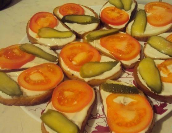 Обжаренный батон смазываем майонезом. Сверху выкладываем помидоры и огурцы.