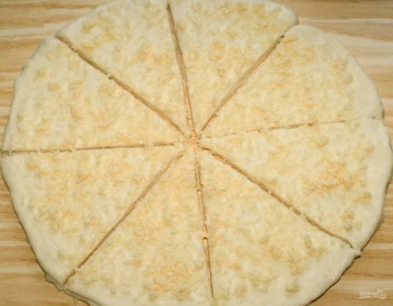 10.Раскатываю вторую часть, смазываю её маслом и посыпаю сыром, выкладываю её на первый пласт, то же самое проделываю и с третьей частью теста. Разрезаю получившуюся трёхслойную лепёшку на равные треугольники.