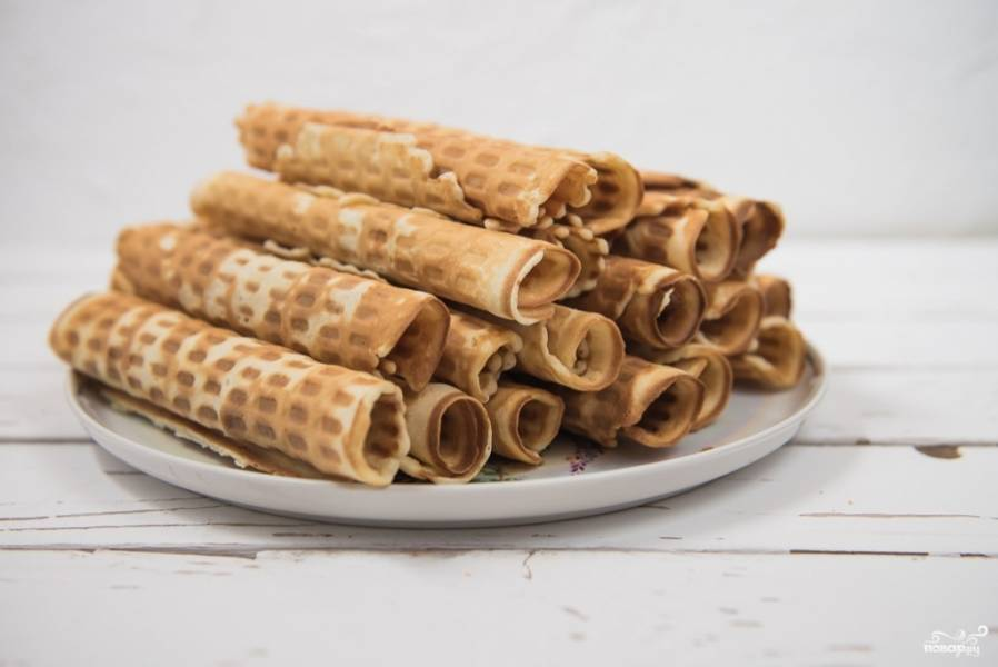 Разогрейте вафельницу, смажьте маслом растительным и выпекайте вафли до готовности. Заверните в трубочки, пока вафли еще горячие.