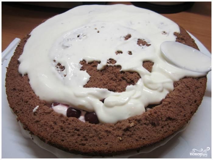 Шаг 9. Сверху выложите крем, размажьте его по всему диаметру. Затем положите целую вторую половинку коричневого бисквита, смажьте кремом. Положите на него белый бисквит, еще раз смажьте кремом.