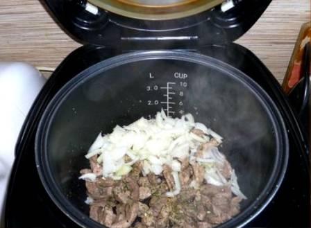 Когда свинина покроется ароматной румяной корочкой, посыпаем ее специями, солим и выкладываем в чашу нарезанный полукольцами репчатый лук. Перемешиваем все и жарим на том же режиме еще 2-3 минуты.
