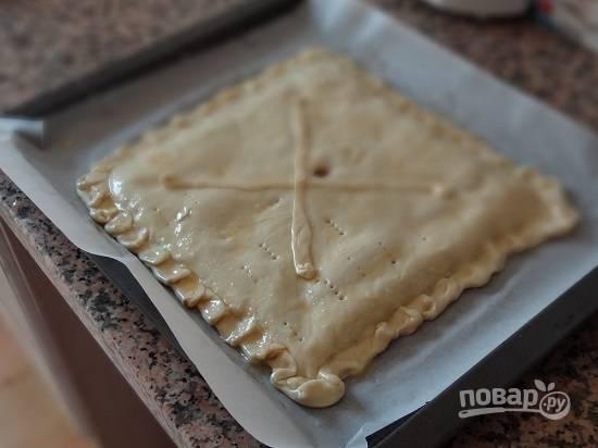 По центру или даже в нескольких местах сделаем в пироге дырочки, чтобы через них выходил пар. Наколем вилкой. Пирог можно украсить полосками теста. Смазываем взбитым яйцом.