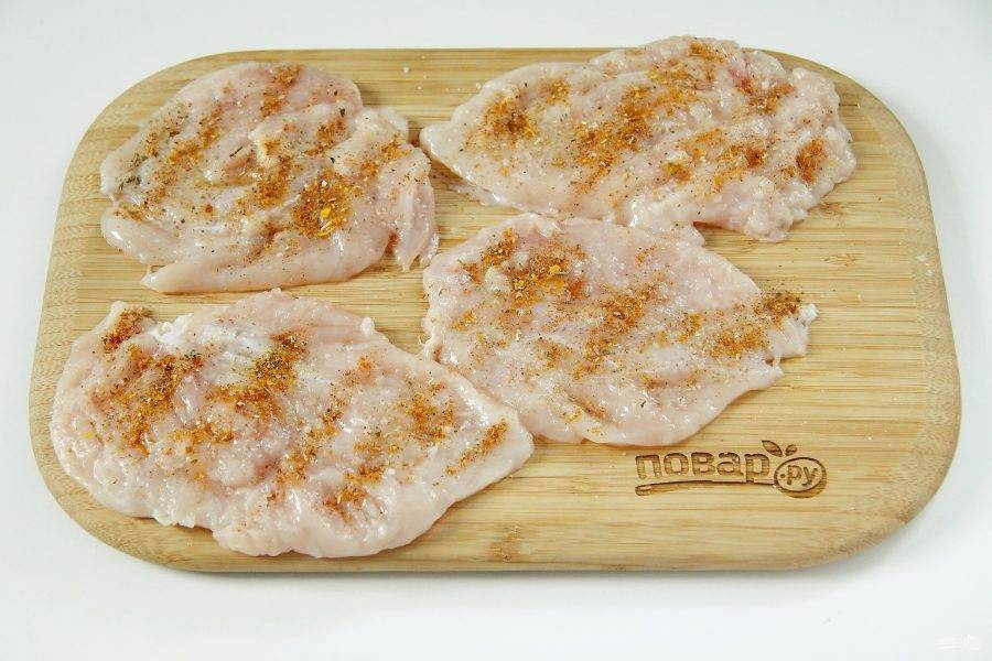 Куриное филе разрежьте вдоль на 2 части. Каждую часть отбейте с двух сторон, посыпьте солью, специями и сбрызните соком лимона.