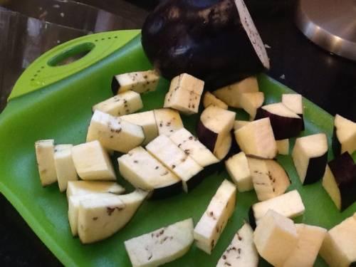 Сначала нужно очистить и нарезать все овощи, не забывая их промыть. Баклажан от кожуры чистить не обязательно, поскольку тот может потерять форму. Нарезаем его на крупные кубики. Перчики очищаем от семечек и нарезаем их дольками. С цуккини поступаем точно также как и с баклажаном. А вот помидоры лучше избавить от кожуры, для этого делаем небольшой надрез и на кожуре и опускаем его на минутку в кипяток. После этого также крупно его нарезаем и присоединяем к остальным овощам. Лук очищаем от шелухи, нарезаем его полукольцами и отправляем к его собратьям по грядке.