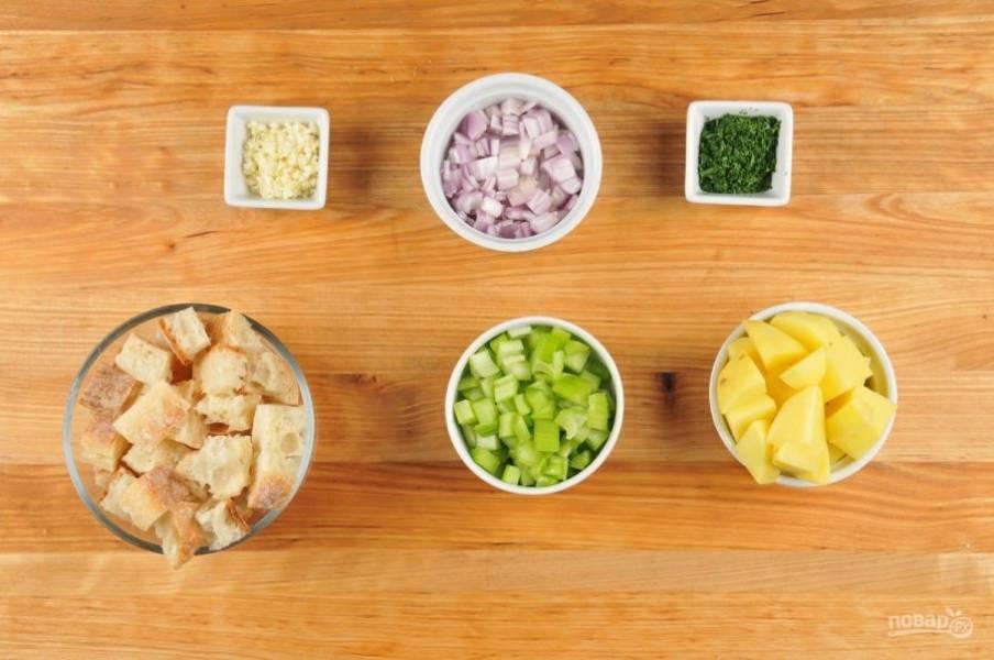 1. Подготовьте ингредиенты. Хлеб и картофель нарежьте кубиками. Чеснок и петрушку измельчите. Сельдерей и лук нашинкуйте небольшими кусочками.