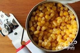 Открыть кукурузу, слить сок и высыпать зерна в миску с капустой.