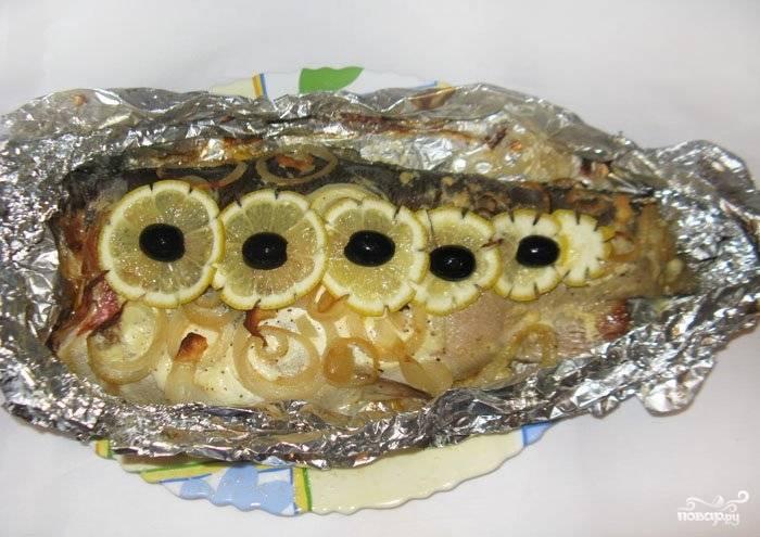 Если тушка весит около килограмма или больше, то запекать её нужно около часа. Затем нужно открыть фольгу и дать рыбе подрумяниться в духовке ещё минут 10-15. Перед подачей украсьте форель лимоном и маслинами.