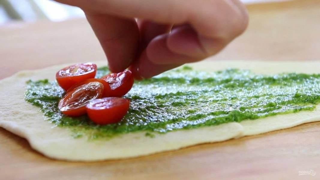 3. Потом выложите на широкую часть теста половинки помидоров и кубики сыра.