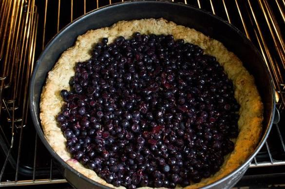 Чернику смешиваем с ложкой сахара и крахмала. Высыпаем ягоды на тесто и выпекаем еще 15 минут.