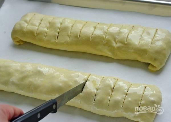 10. Смажьте взбитым яйцом, сделайте надрезы острым ножом. Отправьте противень в разогретую до 180 градусов духовку.