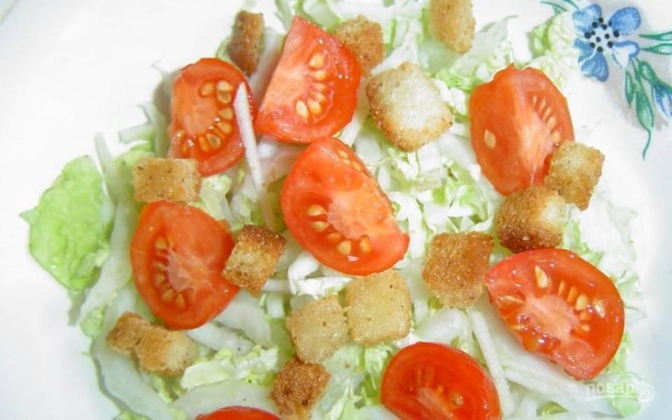 4. В салатник выкладываю пекинскую капусту, добавляю сухарики и томаты, солю.