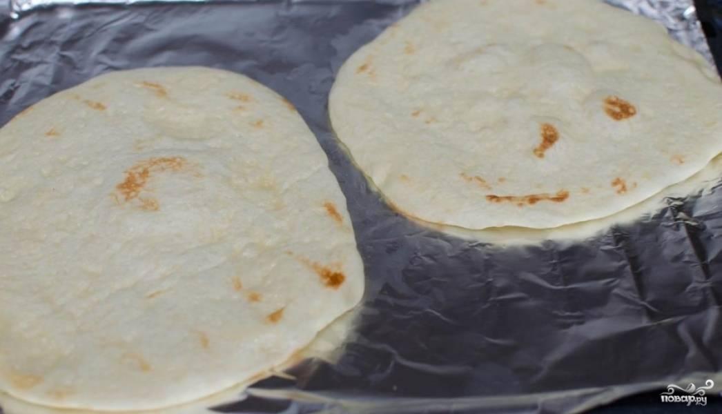 Лепешки выкладываем на противень, затянутый фольгой и отправляем выпекаться в духовку на 2-3 минуты, затем достаем противень, переворачиваем лепешки и выпекаем еще 2-3 минуты.