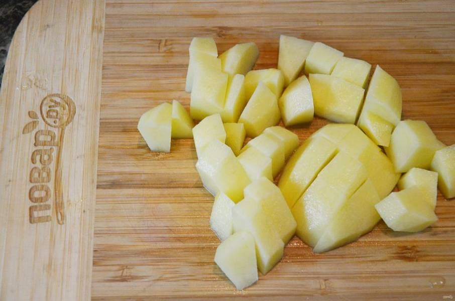 Картофель почистите, нарежьте кубиком и добавьте в кастрюлю.