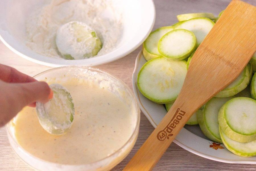 В сковороде разогрейте растительное масло. Колечко кабачка обваляйте в муке, затем в кляре и выкладывайте на сковороду.