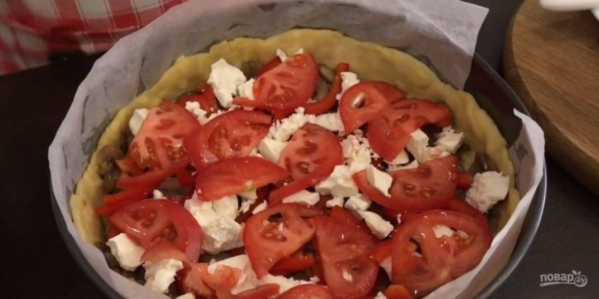 7.  Из слегка остывшей начинки слейте лишнее масло, выложите ее на тесто. Сверху выложите нарезанный болгарский перец, брынзу, помидоры, тертый сыр и заправку из сметаны.