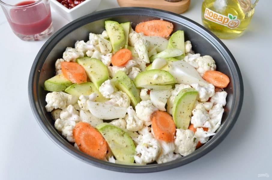 Цветную капусту разберите на соцветия. Лук порежьте на 4 части каждый. Морковь – наискосок тонкими кружочками. Кабачок разрежьте на две половинки и каждую порежьте тонко, примерно 0.5 см в толщину. Каждый зубчик чеснока порежьте на 2 части. Сложите овощи в миску, добавьте соль, перец, прованские травы, ложку масла и перемешайте. Переложите в смазанную форму овощи и запекайте 30 минут при 210-215 градусах. Периодически перемешивайте овощи лопаткой.