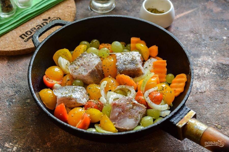 Выложите все ингредиенты в сковороду, добавьте травы, специи и полейте рыбу маслом. Добавьте в емкость воду — 50-70 мл.