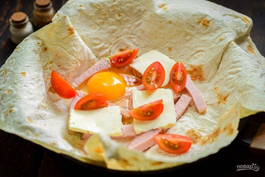 Нарежьте томаты дольками и отправьте в лаваш.