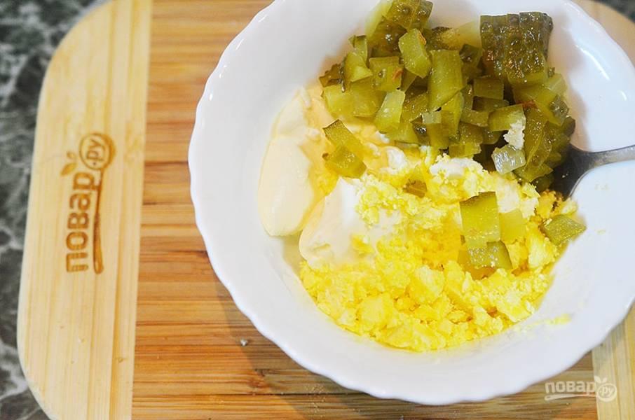 Добавьте к сыру нарезанный огурец. Желток разомните вилкой. Перемешайте.