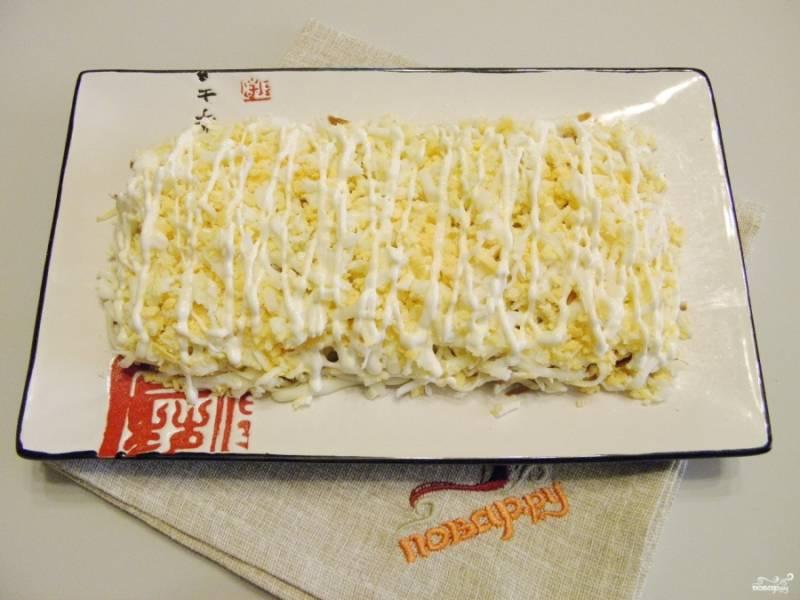 Следующий слой салата - тертые вареные яйца, майонезная сеточка, соль.