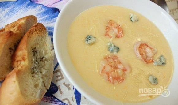 Суп-пюре разлейте по тарелкам, дополните креветками и двумя видами сыра. Подавайте суп с белым багетом. Приятного аппетита!