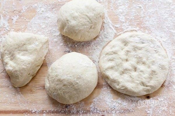 Сперва обомните тесто на присыпанной мукой поверхности. Разделите его на несколько кусков и растяните руками в форме основы для пиццы.