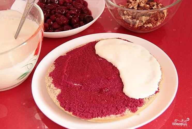 Если от ягоды есть сок, то пропитайте им неразрезанный бисквит. Далее смажьте его кремом, уложите вишню и орехи. Также смажьте кремом кусочки из коржа и выложите их следующим слоем, а сверху добавьте оставшуюся вишню с грецкими орехами. Торт смажьте кремом и уберите в холодильник.
