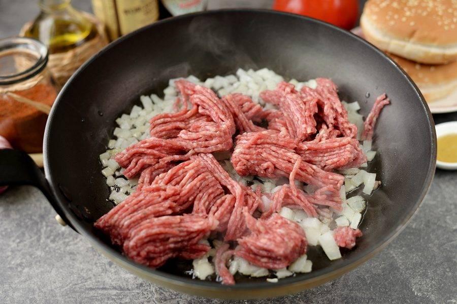 Добавьте говяжий фарш в сковороду, сразу же начинайте активно его помешивать, чтобы он не остался комочками.